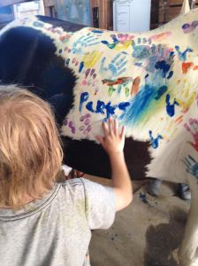 Parks painting a horse at camp.